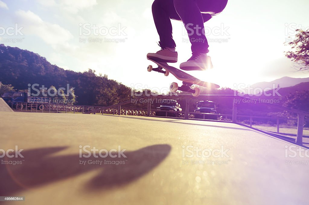 skateboarder legs doing a trick ollie at skatepark stock photo