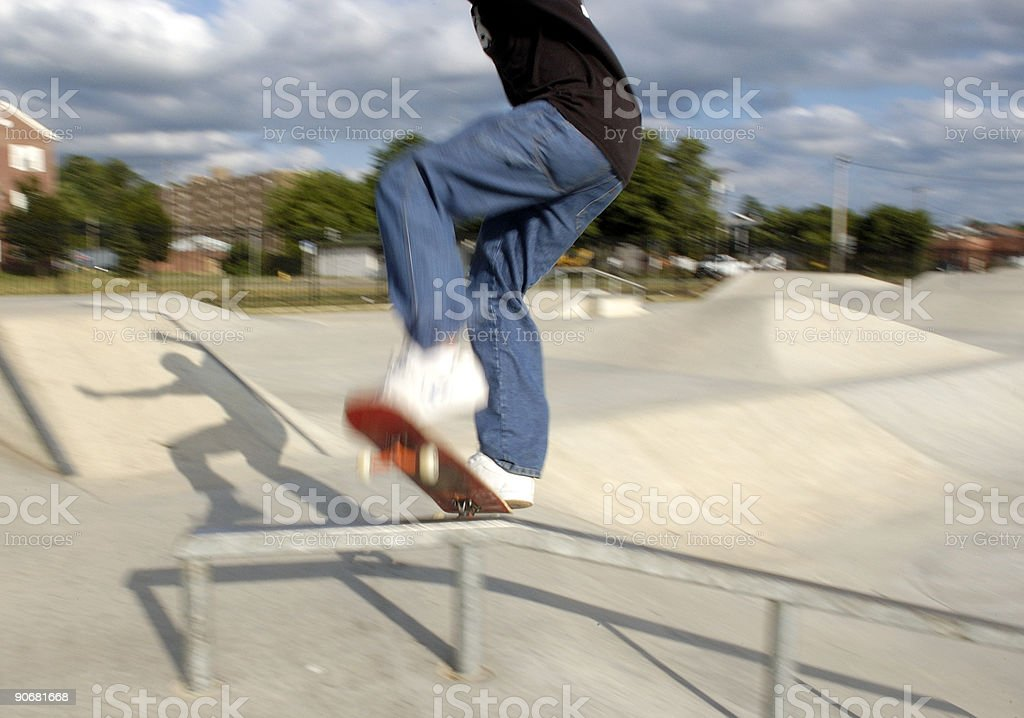 Skateboarder on grind rail stock photo