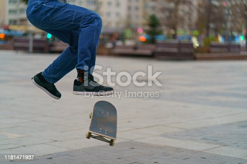 Young skateboarder performs a trick on a city street in autumn day. Young man is jumping. Extreme sports is very popular among youth.