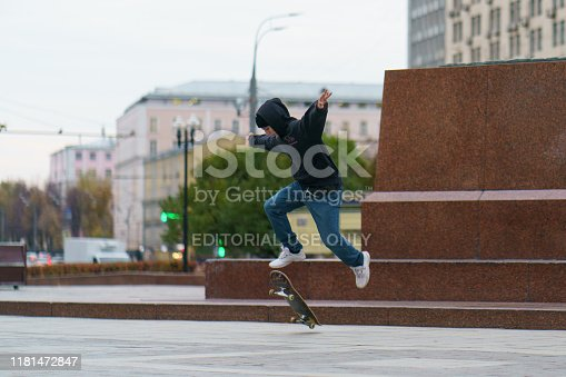Moscow, Russia - October 14 2018:  Young skateboarder performs a trick on a city street in autumn day. Young man is jumping. Extreme sports is very popular among youth.