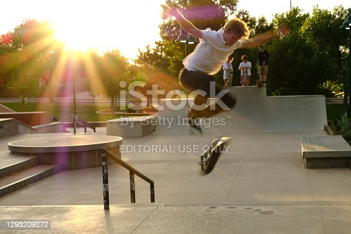 Santa Fe, NM USA -- July 30, 2019: As the sun sets, an unidentified skateboarder practices his jump and flip tricks. Because of his pose, it almost looks as though he is flying.