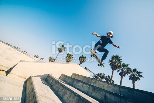 Action shot of performing 14 year old African-American skateboarder in Los Angeles on Venice Beach skate park, high ISO grain added. Palm trees and Venice Beach are in the background.
