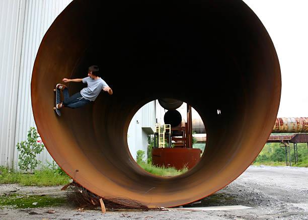 Skateboarder riding full pipe stock photo