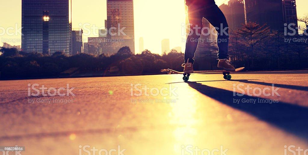 Skatista skate ao nascer do sol na cidade foto royalty-free