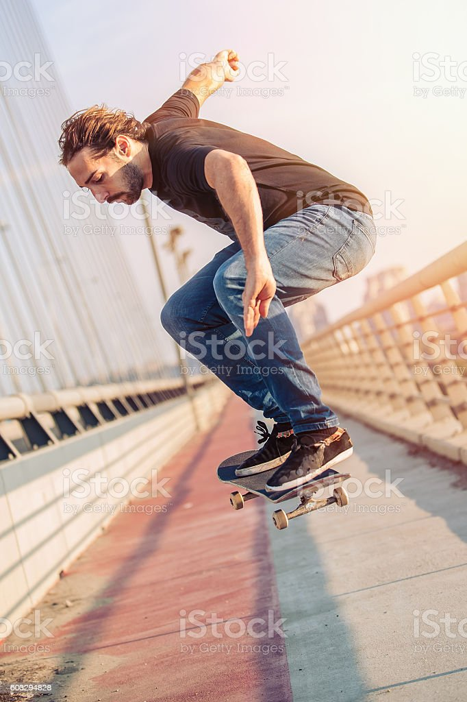 Skateboarder skates and doing jumps over a city bridge stock photo