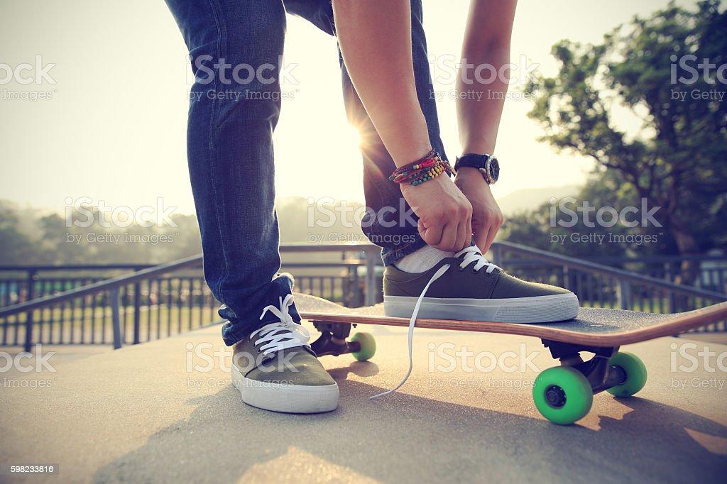 Skatista tying cadarço na pista de skate rampa foto royalty-free