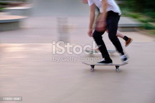 At sunset, skateboarders practice their tricks in skate park. Motion blur.