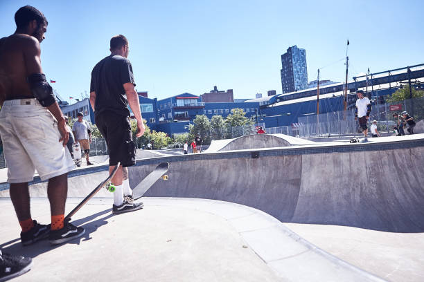 Skateboarders standing by a deep concrete bowl stock photo