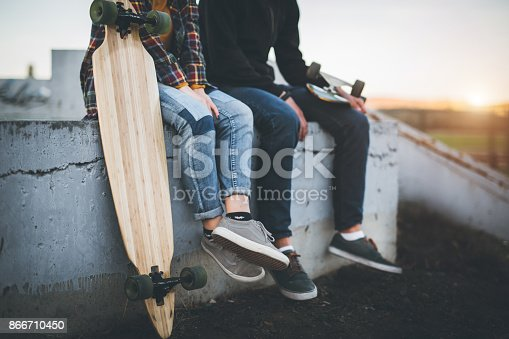 Young skateboarders sitting on concrete and taking a rest from ride.