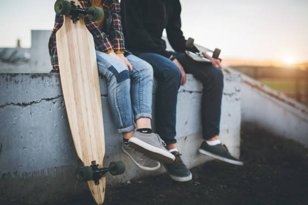 skateboarders taking a rest in skate park - skateboard stock pictures, royalty-free photos & images