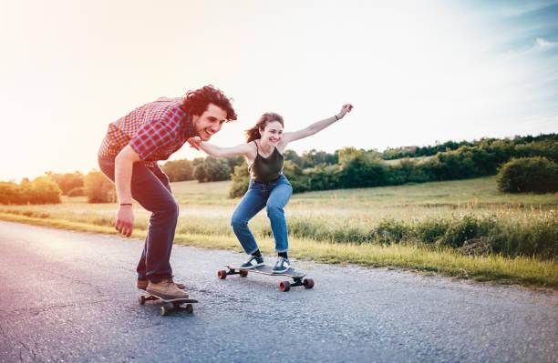 Skateboarding couple having fun stock photo