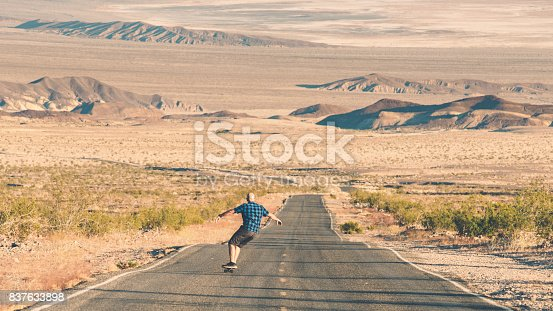 Lone Skateboarder riding down hill in Death Valley National Park
