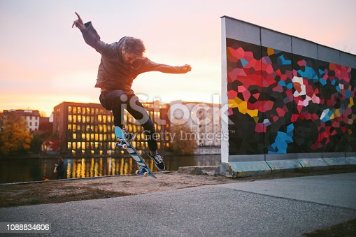 *** NOTE TO INSPECTOR IN THE DESCRIPTION !!!!!!!!!!!!!!!!  Young man skateboarding in Berlin by the Spree river. He is wearing casual skateboarding clothing, a hoodie and skate shoes, practicing kickflip, ollie and other tricks. Taken on a nice Autumn day, just as the sun sets in Berlin's Friedrichshain - Kreuzberg district near the remaining parts of the Berlin Wall.  ***** HELLO. THERE IS A PROPERTY RELEASE FOR THE ARTWORK THAT I HAVE DONE IN PHOTOSHOP AND ATTACHED TO THE WALL TO LOOK LIKE A GRAFFITI. IT IS NOT AN ACTUAL GRAFFITI. THANK YOU.