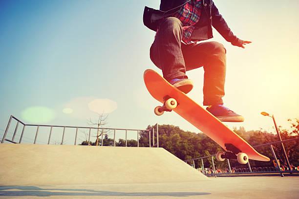 skateboarding  jumping at  sunrise stock photo