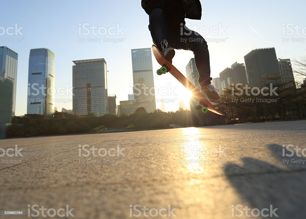 skateboarding legs doing an ollie trick at sunrise city stock photo