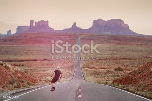Lone Skateboarder riding down hill in Monument Valley National Park