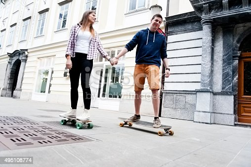 Young couple with skateboards in the city. Man is teaching his girlfriend how to do it.