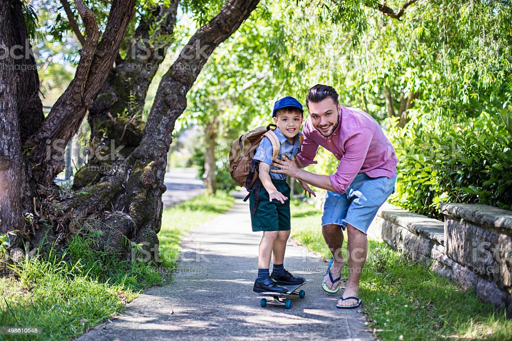 Skateboarding to school with daddy stock photo