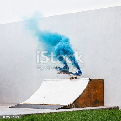 Skateboarder vanishes into blue smoke while performing a trick on DIY quarter pipe ramp