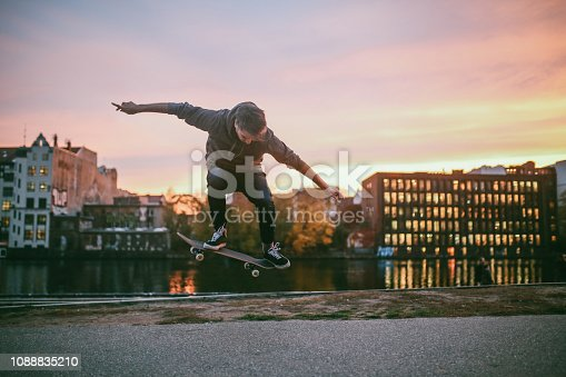 Young man skateboarding in Berlin by the Spree river. He is wearing casual skateboarding clothing, a hoodie and skate shoes, practicing kickflip, ollie and other tricks. Taken on a nice Autumn day, just as the sun sets in Berlin's Friedrichshain - Kreuzberg district near the remaining parts of the Berlin Wall.