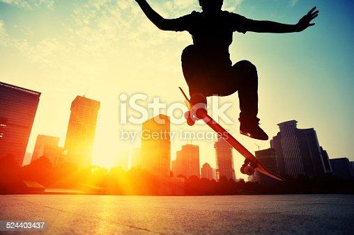 skateboarding  woman jumping at  sunrise city