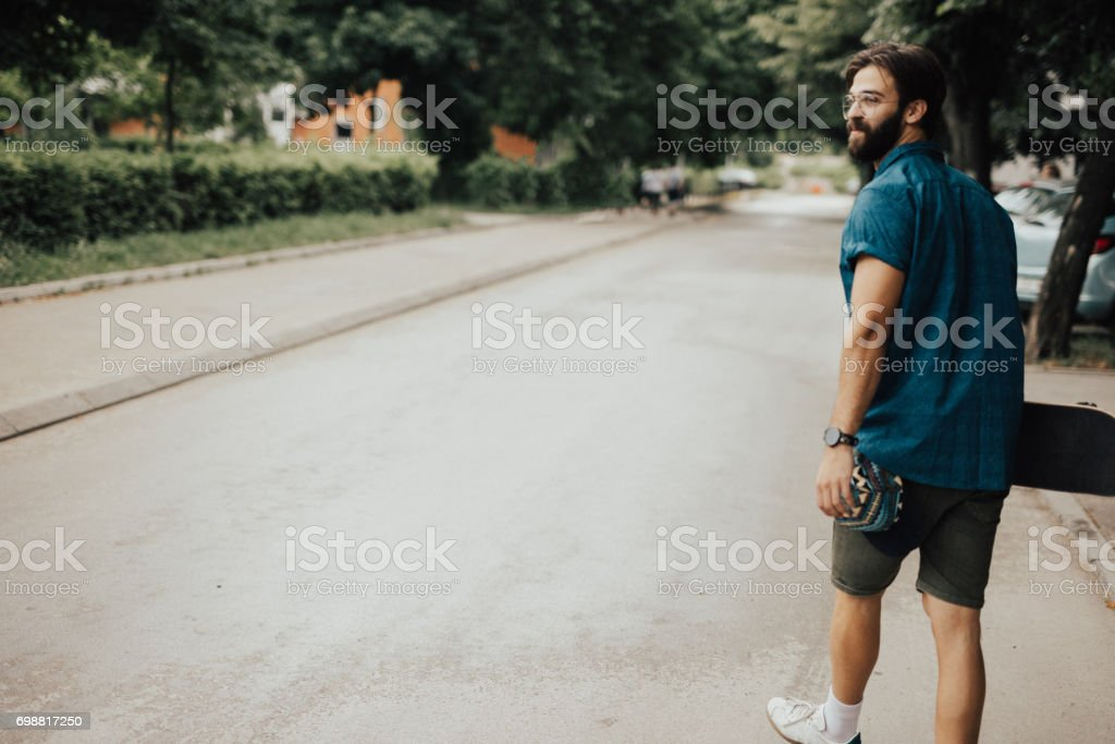 Skateborader crossing the street on foot stock photo