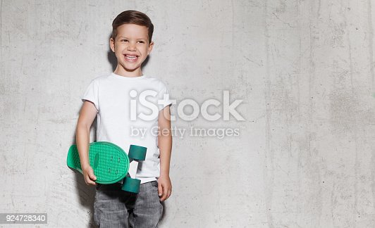 istock Skater boy in white T-shirt, concrete wall on background 924728340