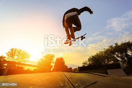 Silhouette of a young skater jumping with skateboard at a skate park at sunset. About 25 years old, Caucasian male.