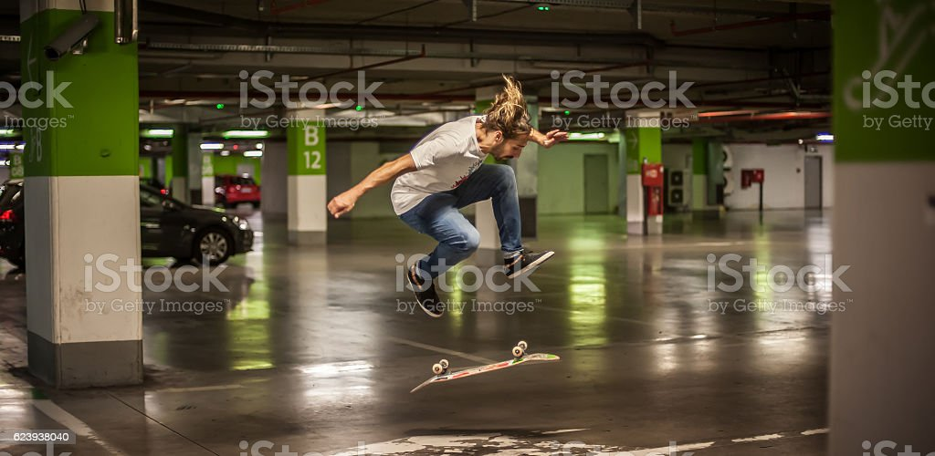 Skater doing tricks and jumping in the underground garage stock photo