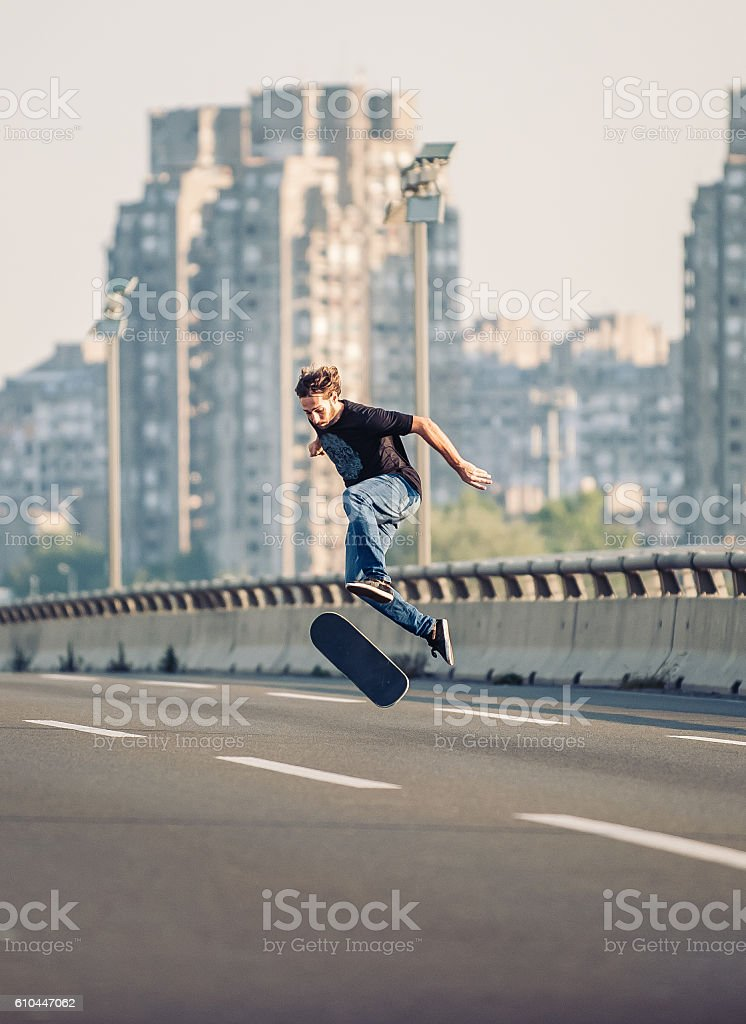 Skater doing tricks and jumping on the street highway bridge stock photo