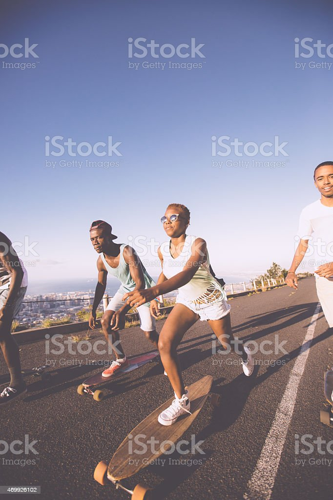 Skater girl downhill racing on her longboard with friends stock photo