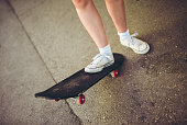 Young female skater driving skateboard on the streets
