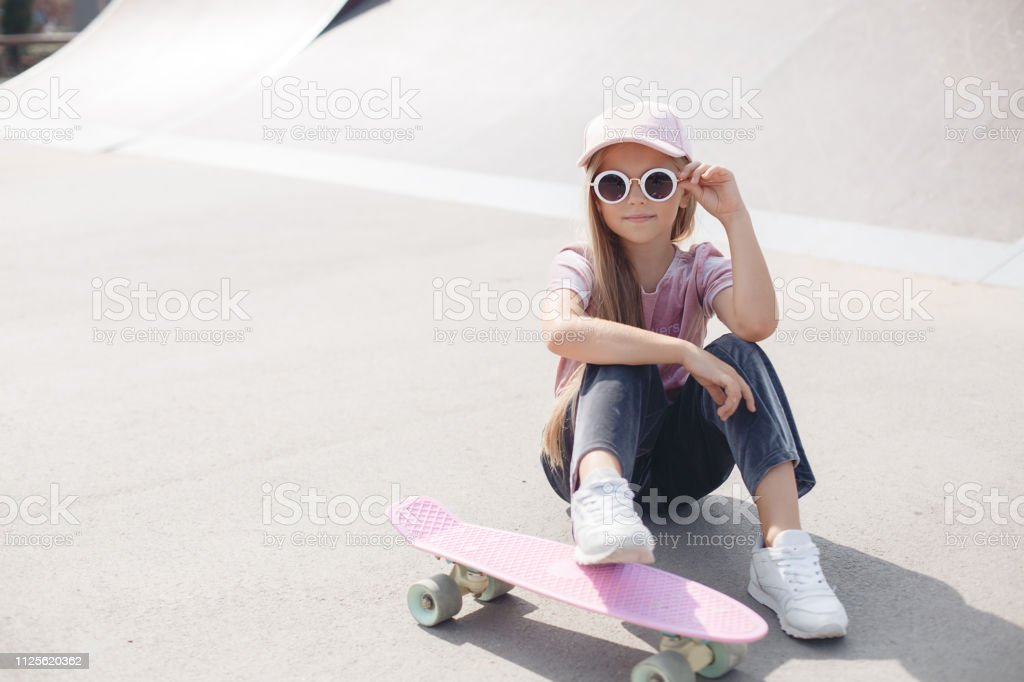 Skater girl on outdoors.Pretty young long-haired blond child girl in...