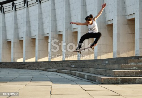 young skateboarder woman jumping from stair. Slight motion blur.
