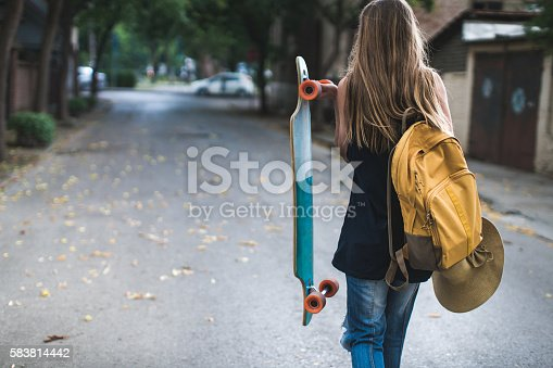 Girl with a backpack holding a longboard walking on the street