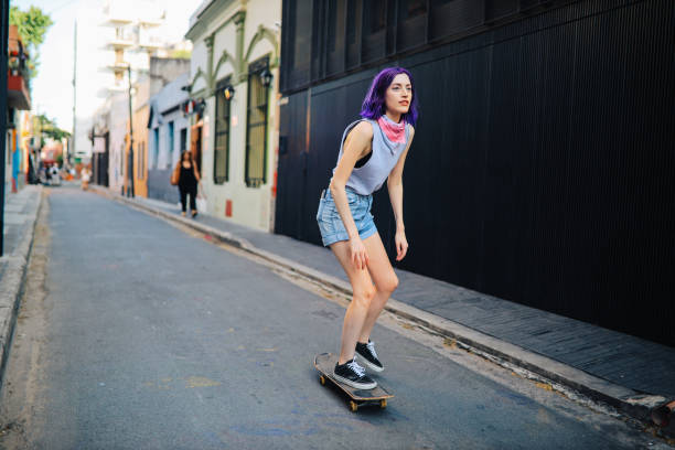 skater girl riding in the streets of buenos aires - showus стоковые фото и изображения