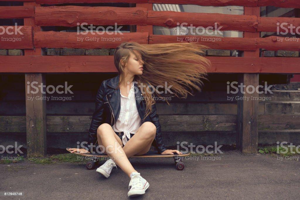 fille de patineur assise dans le parc - Photo