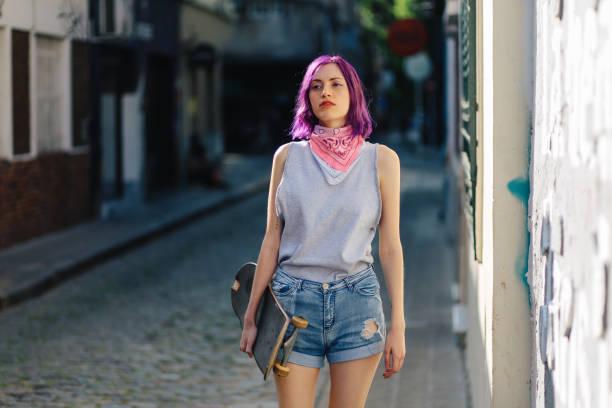 skater girl walking down the street - showus стоковые фото и изображения