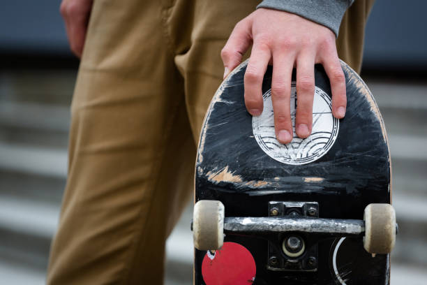 Skater hand holding skateboard deck in an urban surroundings outdoors stock photo