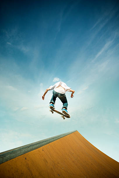 skater in jump over skating poligon ramp - skateboarding stock pictures, royalty-free photos & images