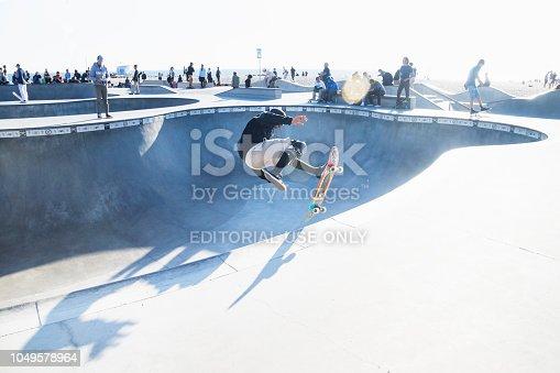 Venice Beach, Los Angeles, California - February 25 2018: Skater jumping at halfpipe with backlight at Venice Beach skatepark at a sunny day
