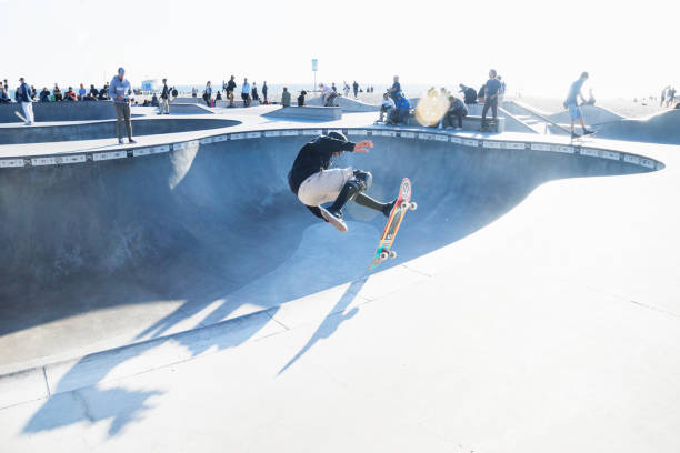 Skater jumping at halfpipe with backlight at Venice Beach skatepark, Venice Beach, Los Angeles, California stock photo