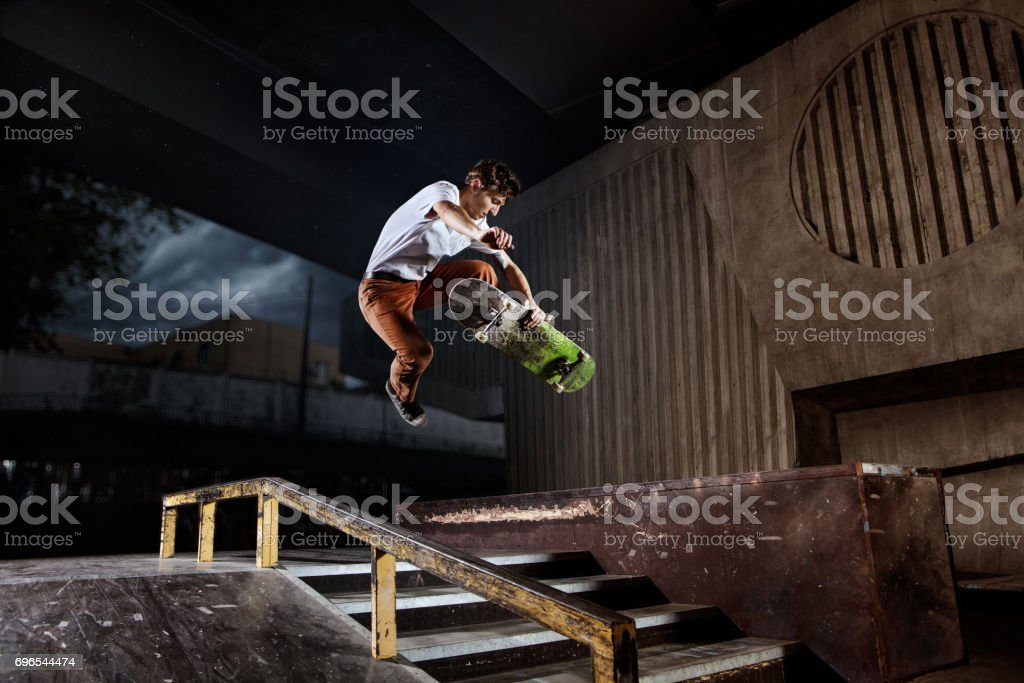 Skater jumping on his skate in skatepark stock photo