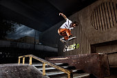 Skater jumping on his skate in skatepark. The guy performs a complicated trick. He flies in the air on his skate.