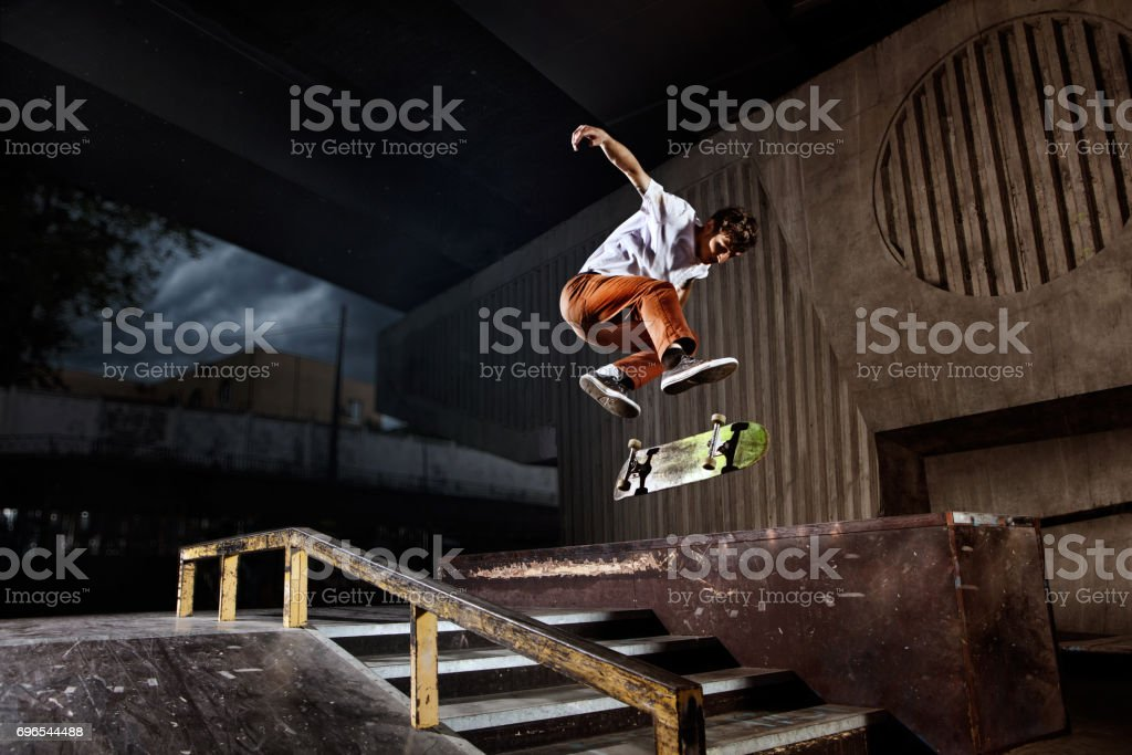 Skater jumping on his skate in skatepark stock photo