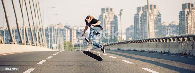 Skater doing tricks and jumping on the street highway bridge, through urban traffic. Free riding skateboard. Panorama view