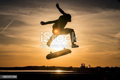 Skater jump on asphalt road and make trick kickflip against the beautiful orange sunset