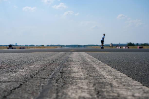 schaatser op lege asfaltweg / landingsbaan op de voormalige vliegveld - laag camerastandpunt stockfoto's en -beelden