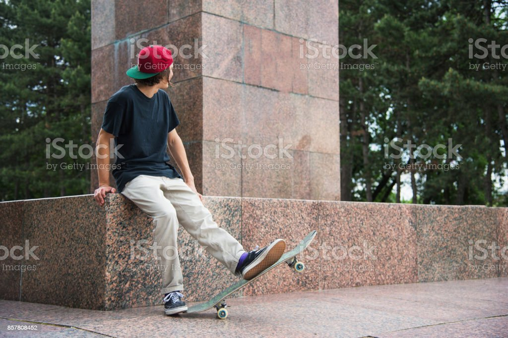 Skater sits with his back and thinks next to the skateboard stock photo