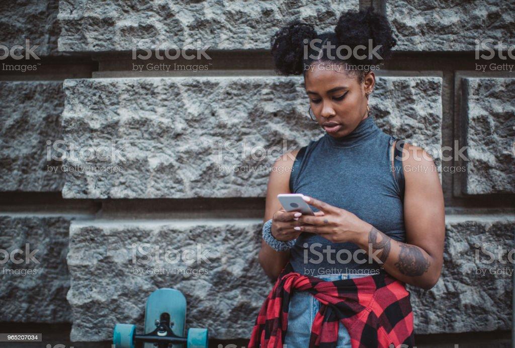 Skater using phone on street zbiór zdjęć royalty-free